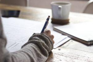 ノートにメモする女性の手